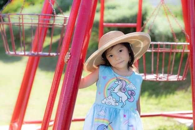 Śliczna mała dziewczynka jest ubranym dużego kapelusz i bawić się w plenerowym parku