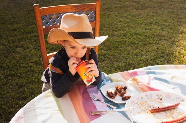 Śliczna mała dziewczynka jest ubranym kapelusz pije sok