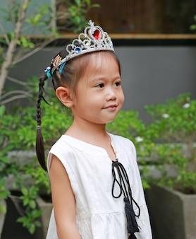 Śliczna mała dziewczynka jest ubranym koronę i białą suknię śliczny ono uśmiecha się