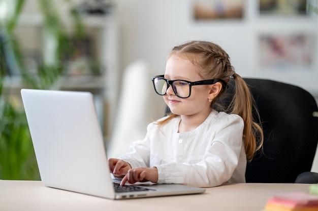 Śliczna mała dziewczynka jest ubranym szkła używać laptopu elektronicznego e-learningowego pojęcie