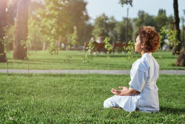 Śliczna mała dziewczynka karateka robi ćwiczenia medytacyjne na świeżym powietrzu