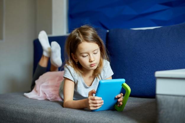 Śliczna mała dziewczynka leży na kanapie, dziecko uzależnione od technologii, grając w gry online na komputerze typu tablet, używając aplikacji