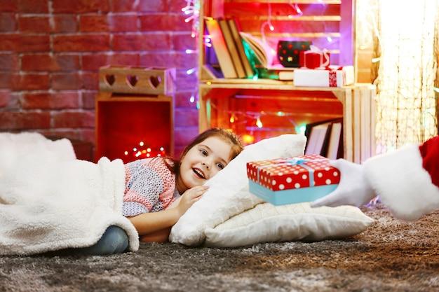 Śliczna mała dziewczynka leży na poduszce pod miękką kratą, czeka na prezent od mikołaja w świątecznym pokoju