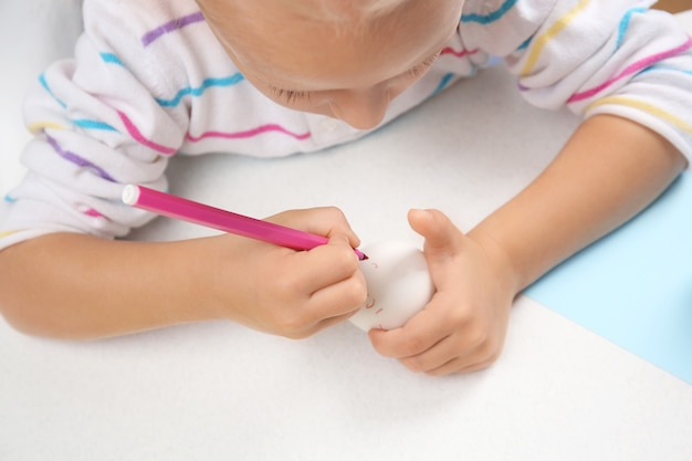 Śliczna mała dziewczynka maluje jajko na wielkanoc siedząc przy stole
