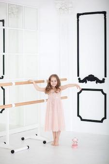 Śliczna mała dziewczynka marzy o zostaniu baletnicą. dziecko dziewczynka w różowej sukience taniec w pokoju. dziewczynka studiuje balet. mała dziewczynka trzyma muzyczną zabawkarską karuzelę. sala klasy sali baletowej