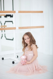 Śliczna mała dziewczynka marzy o zostaniu baletnicą. mała baletnica w sukience siedzi w klasie tańca na podłodze. dziewczyna studiuje balet. mała dziewczynka trzyma muzyczną zabawkarską karuzelę. sala baletowa