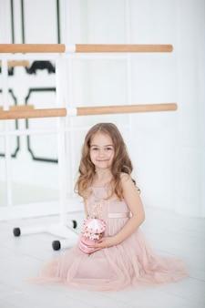 Śliczna mała dziewczynka marzy o zostaniu baletnicą. mała baletnica w sukience siedzi w klasie tańca na podłodze. dziewczynka studiuje balet. mała dziewczynka trzyma muzyczną zabawkarską karuzelę. sala baletowa