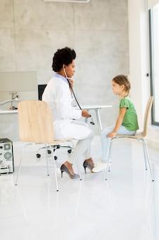 Śliczna mała dziewczynka na egzaminie pediatry przez afroamerykańską lekarkę