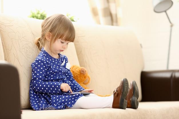 Śliczna mała dziewczynka na kanapie używa telefonu komórkowego