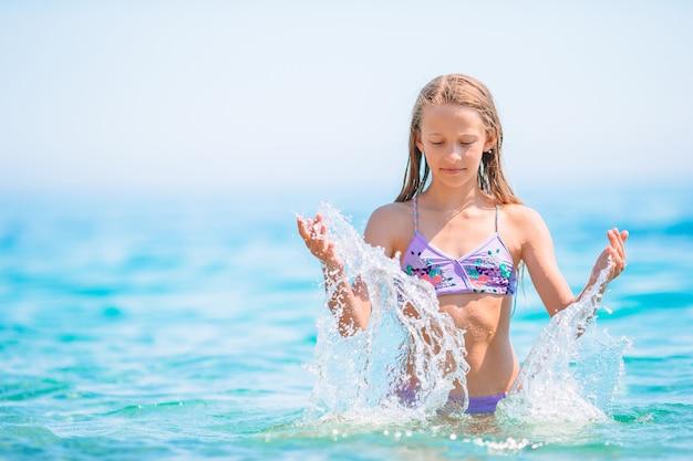Śliczna mała dziewczynka na plaży podczas letnich wakacji