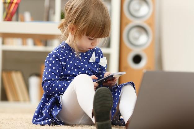 Śliczna mała dziewczynka na podłogowym dywanowym use telefonie komórkowym