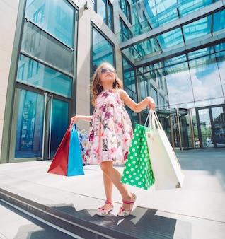 Śliczna mała dziewczynka na zakupy. portret dziecka z torby na zakupy. zakupy. dziewczyna.