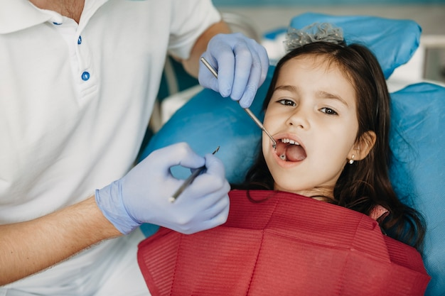 Śliczna mała dziewczynka o bólu zęba robi badanie zębów u dentysty dziecięcego.