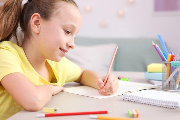 Śliczna mała dziewczynka odrabia pracę domową we wnętrzu pokoju