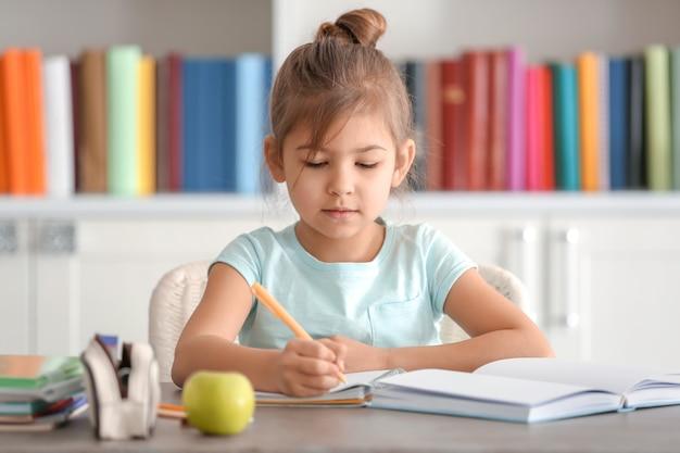 Śliczna mała dziewczynka odrabiania lekcji w pomieszczeniu