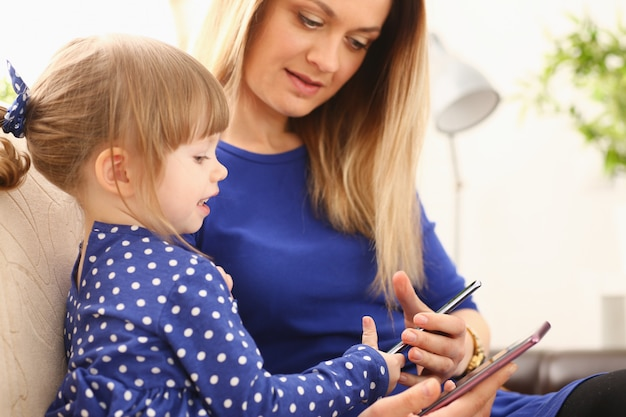 Śliczna mała dziewczynka ogląda telefon komórkowy z mamą