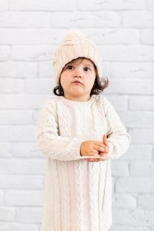 Śliczna mała dziewczynka patrzeje fotografa