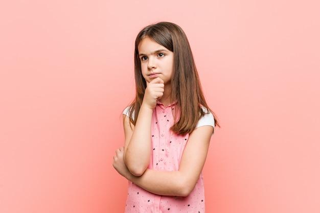 Śliczna mała dziewczynka patrzeje z ukosa z wątpliwym i sceptycznym wyrażeniem.