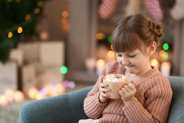 Śliczna mała dziewczynka pije gorącą czekoladę w domu w wigilię bożego narodzenia