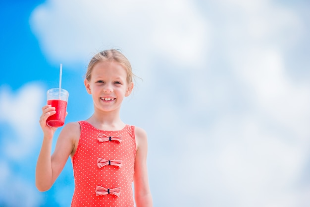 Śliczna mała dziewczynka pije koktajl na tropikalnej plaży