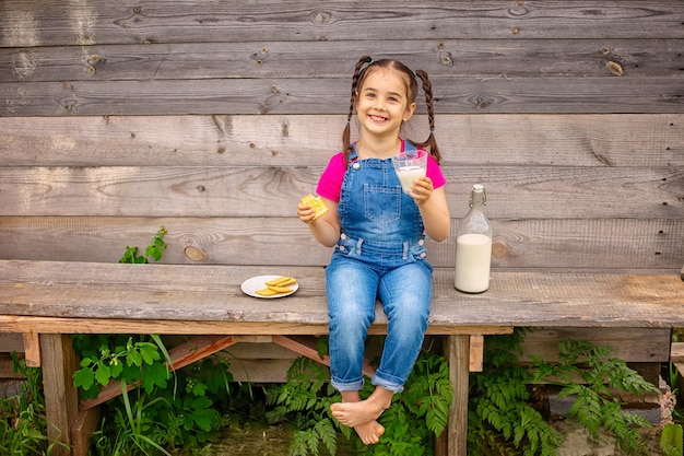 Śliczna mała dziewczynka pije mleko na wsi