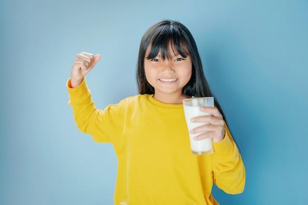Śliczna mała dziewczynka pije mleko w szkle z ono uśmiecha się szczęśliwy