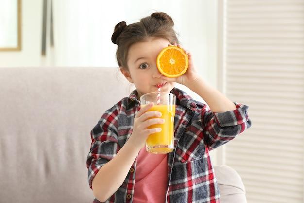 Śliczna mała dziewczynka pije sok siedząc na kanapie w domu