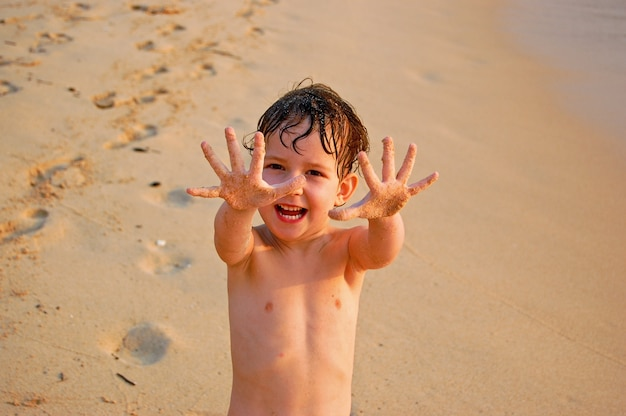 Śliczna mała dziewczynka pokazuje jej ręki na plaży