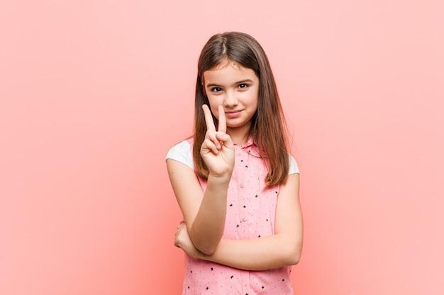 Śliczna mała dziewczynka pokazuje numer dwa z palcami.