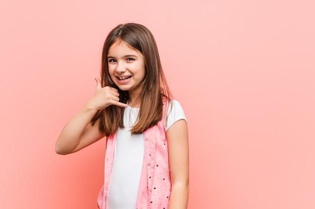 Śliczna mała dziewczynka pokazuje telefonu komórkowego wezwania gest z palcami