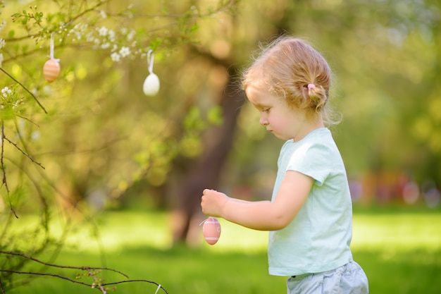 Śliczna mała dziewczynka poluje dla easter jajka na gałęziastym kwiatonośnym drzewie.