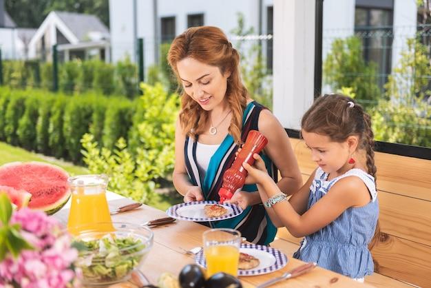Śliczna mała dziewczynka pomaga matce kładąc keczup na jej talerzu