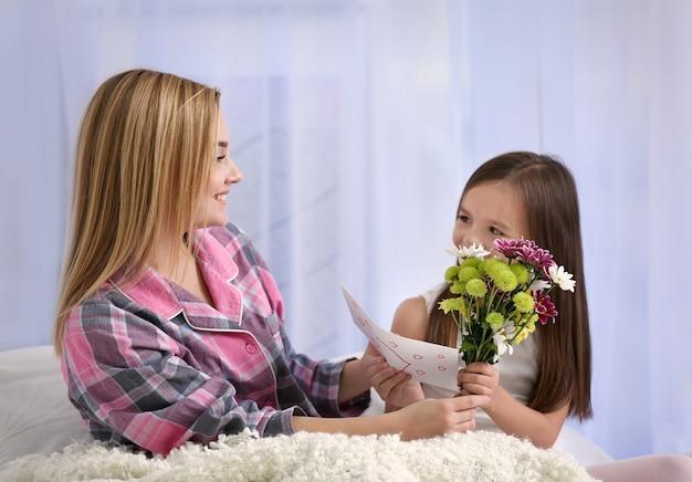 Śliczna mała dziewczynka pozdrawia matkę w domu. koncepcja dnia matki