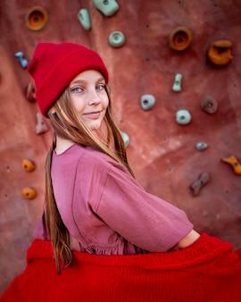 Śliczna mała dziewczynka pozuje obok ściany wspinaczkowej