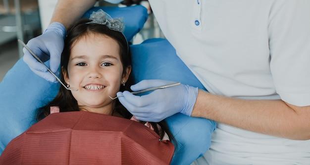 Śliczna mała dziewczynka przed badaniem zęba przez stomatologa dziecięcego.