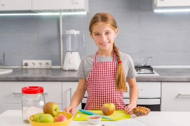 Śliczna mała dziewczynka przygotowywa gotować jabłczanego strudel