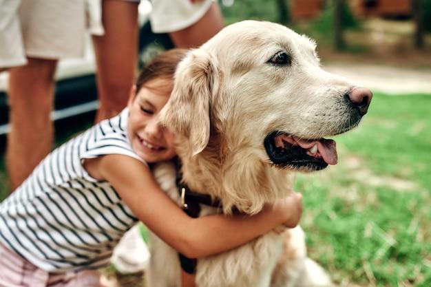 Śliczna mała dziewczynka przytula psa labrador. rodzina na weekend. odpoczywaj na łonie natury. wypoczynek, podróże, turystyka.