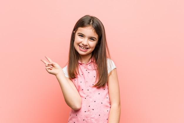 Śliczna mała dziewczynka radosna i beztroska pokazuje znaka pokoju palcami.