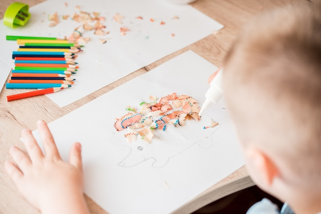 Śliczna mała dziewczynka robi aplikacji klei kolorowemu domowi, nakładając kolorowy papier za pomocą kleju, wykonując dzieła sztuki i rzemiosła w przedszkolu lub w domu. pomysł na kreatywność dzieci, projekt artystyczny wykonany z papieru.