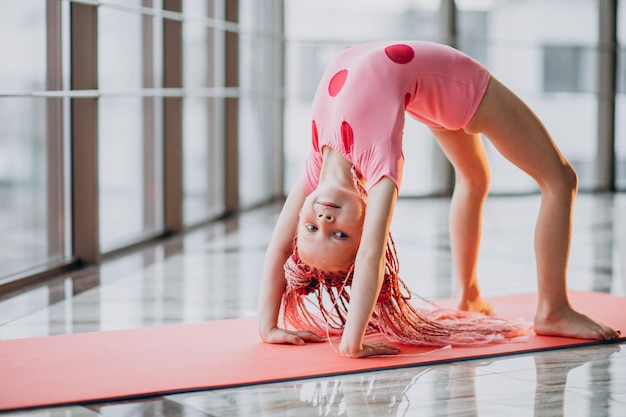 Śliczna mała dziewczynka robi gimnastykom na macie