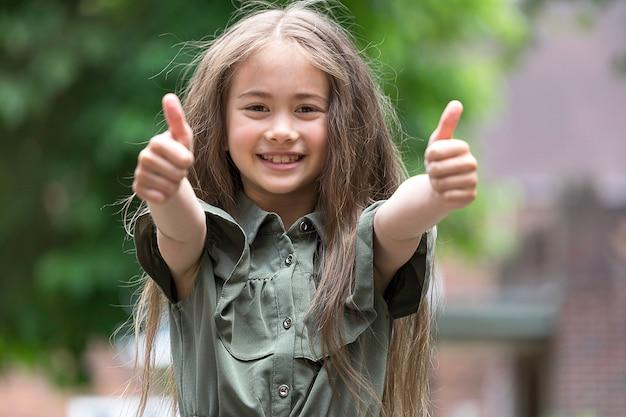 Śliczna mała dziewczynka robi kciukowi up ono uśmiecha się i znakowi
