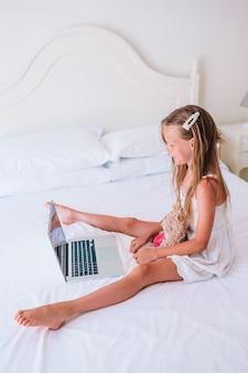Śliczna mała dziewczynka robi pracie domowej na laptopie