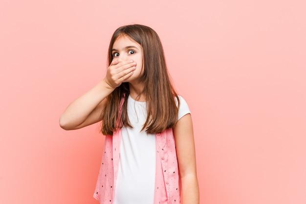 Śliczna mała dziewczynka rozważna patrzeć odbitkowa przestrzeń zakrywa usta z ręką.
