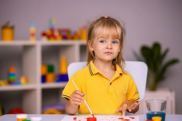 Śliczna mała dziewczynka rysuje farbami w przedszkolu