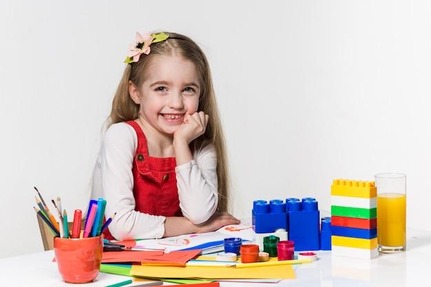 Śliczna mała dziewczynka rysunek farbą i pędzlem w domu