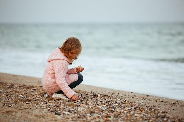 Śliczna mała dziewczynka rzuca skały