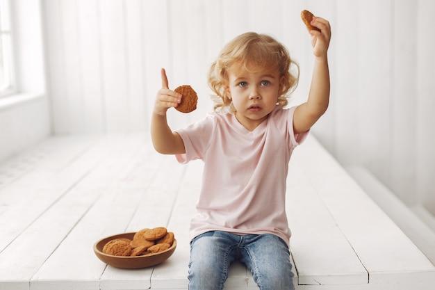 Śliczna mała dziewczynka siedzi ciastka i je