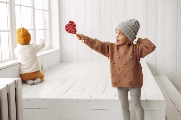Śliczna mała dziewczynka siedzi cukierek i je