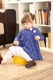 Śliczna mała dziewczynka siedzi na jej sala garnku