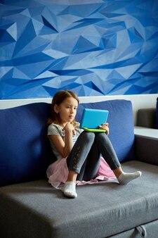 Śliczna mała dziewczynka siedzi na kanapie, dziecko uzależnione od technologii, grając w gry online na komputerze typu tablet, używając aplikacji